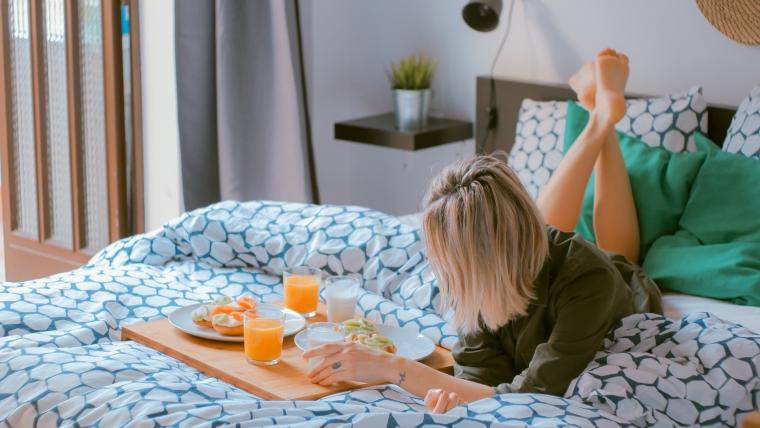 Hotel Hacks - Frau isst auf ihrem Bett im Hotelzimmer